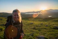 Open landscape of Midnight sun in Lapland Northern Sweden, Europe. Happy Female Hiker enjoy the Midnight Sun north of the Arctic Circle.