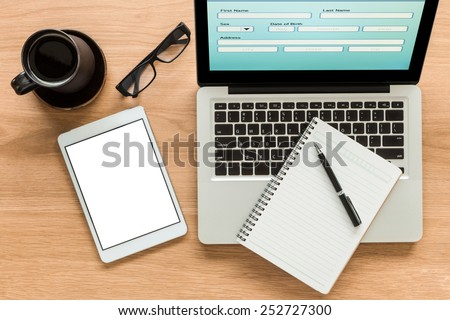 Open laptop shows blank information form and  digital tablet with isolate screen on wooden table. Blank diary on laptop, glasses and a cup of coffee on workspace. Top view image for mock up concept.
