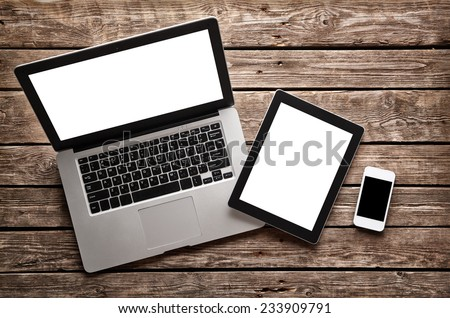 Open laptop with digital tablet and white smartphone. All with isolated screen on old wooden desk. #233909791