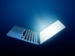 Open laptop with glowing light on dark background