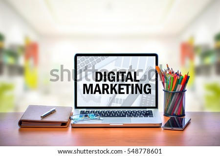 Open laptop with isolated white screen on old wooden desk with text DIGITAL MARKETING