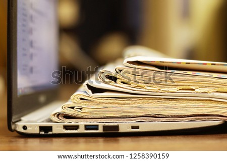 Open Laptop with Newspapers and Magazines on its Keypad. Business Journals with Headlines and Articles and Computer. News by Modern Gadget or Old-fashioned Tabloid Papers                     #1258390159