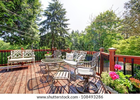 Open large deck with chairs and table home exterior with trees on the back.