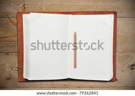 Open Leather Book with Vintage Pencil on Old Wooden Table