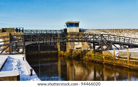 Open lock gate and small bridge over lock chamber close to Ribe River in Denmark.