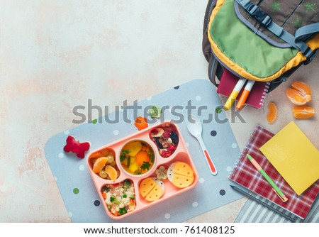 Open lunch box with healthy kid's lunch with vegetable soup, couscous salad and funny sandwiches near school backpack on beige background with blank space for text; top view, flat lay