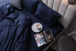 Open magazine and cup of coffee on bed with stylish silky linens in room, above view