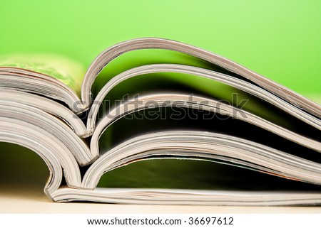 Open magazines in composition lying on table on green backgorund