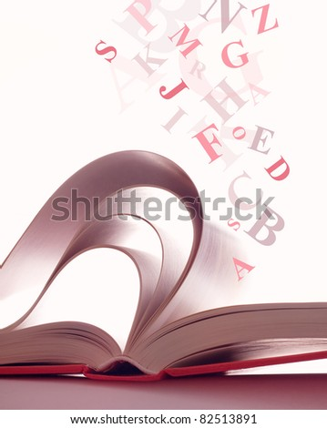 Open magic book with the letters