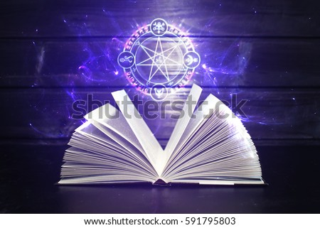 Open magical book with pages like a fan is on the table out comes a colorful light and magic sign. The concept of fantasy and witchcraft #591795803