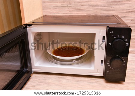open microwave with soup inside. Image of the microwave oven. Modern microwave oven at home