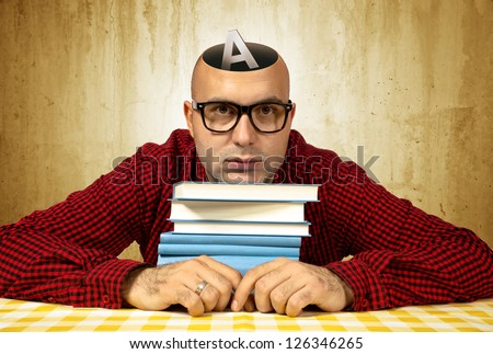 Open minded student with few books sitting at the table, letter A rising from his head.
