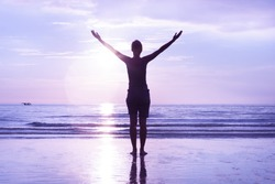 Open mindedness and happiness concept. Woman's silhouette on sunset beach. Stretched out hands to the sky.