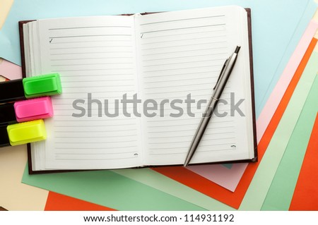 Open note book with lined pages free date space and ballpoint pen and markers.