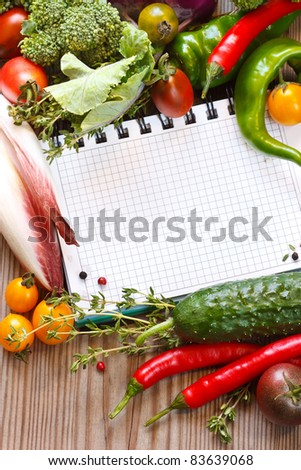 Open notebook and fresh garden vegetables and herbs. #83639068