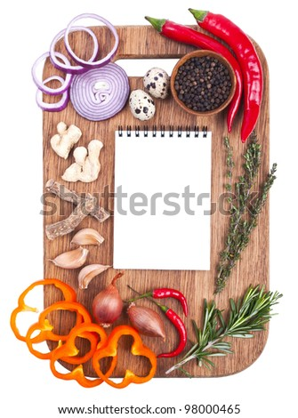 Open notebook and fresh vegetables on an old wooden cutting board. Isolated on white