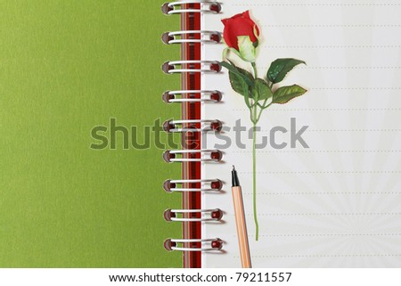 open notebook and red rose