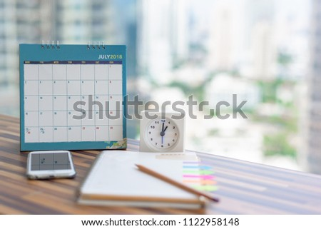 Open Notebook Calendar July 2018 with smartphone diary clock pencil blurred background modern office. Event organizer midyear half year planning, timetable, schedule copy space. Calendar 2018 Concept.