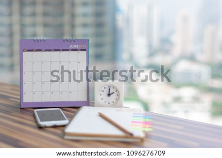 Open Notebook Calendar June 2018 with smartphone diary clock pencil blurred background modern office. Event organizer midyear half year planning, timetable, schedule. Calendar 2018 Concept.