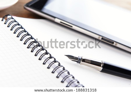 open notebook, mobile  phone and black  pen on white background