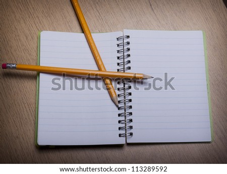 open  notebook on a wooden desk with pencil