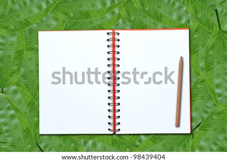 Open notebook on green leaves background