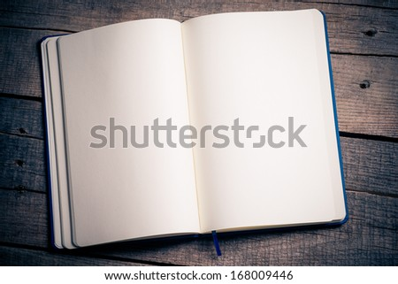 Open notebook on wood background.  - stock photo