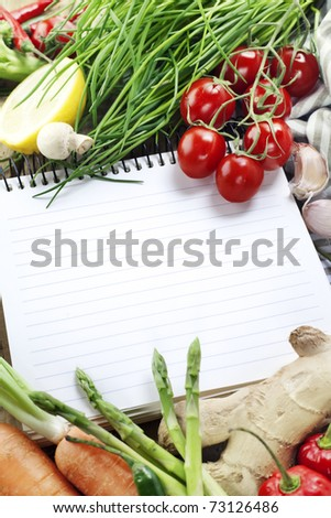 Open notebook (or empty cookbook ready for recipe) and fresh vegetables