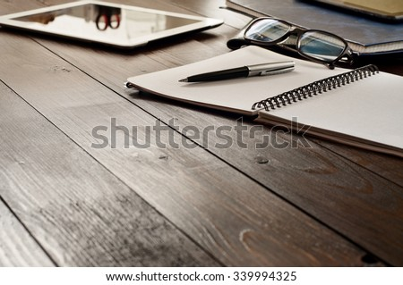 Open notebook, tablet computer, glasses and folders on the office table. Top view with copy space. Free space for text. Office workplace