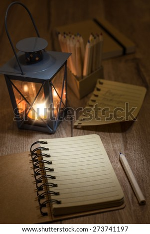 Open notebook with blank front page, candle in metal vintage lantern, torn-out page and a pencil on wooden table. Space for your notes, recipe or a poem on the page.