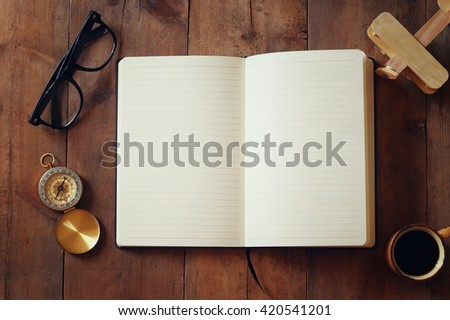 Photo of open notebook with blank pages on wooden table. Top view. Copy space. for text. vintage style image