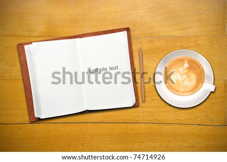 Open notebook with cup of coffee