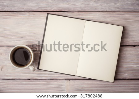 Open notebook with cup of coffee on wooden desk