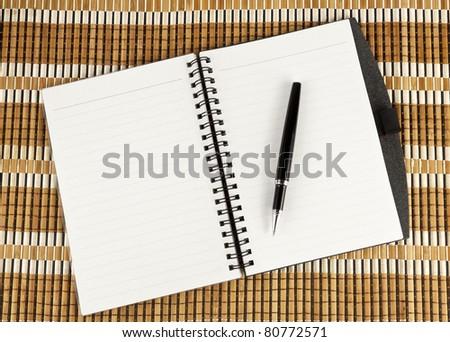 Open notebook with pen over textured bamboo mat