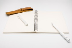 Open notebook with pencil rubber and pencilcase on light grey background