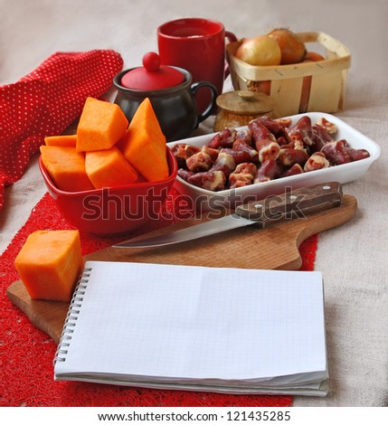 Open notebook with raw chicken hearts and ingredients for dinner