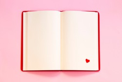 open notebook with red heart on pink background