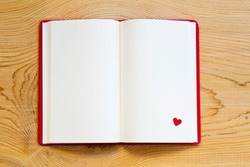 open notebook with red heart on wood background. top view.