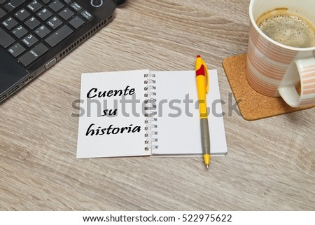 """Open notebook with Spanish text """"CUENTE SU HISTORIA"""" (Tell Your story) and a cup of coffee on wooden background. Top down view #522975622"""