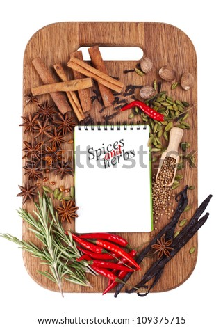 Open notebook with spices and herbs on the old wooden cutting board. Isolated on white.