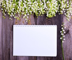 open notebook with white blank sheets on a gray wooden background, a fan of a bouquet of blossoming lilies of the valley