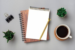open notepad, cup of coffee, succulents, golden pen on gray background, spiral notebook on table Business, planning, education, morning life working from home concept Top view Flat lay Mock up