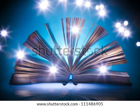 Open old book, mystical blue light at background, light painting