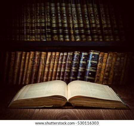 Open old book on a bookshelf background. Selective focus.