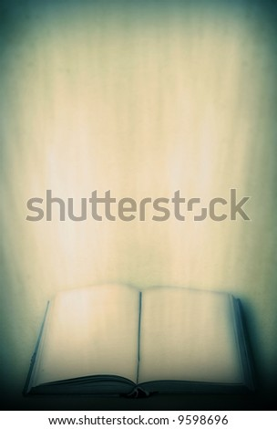 Open old book with light beams coming out of its pages stock photo