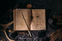Open old book with magic spells, runes, black candles on witch table. Occult, esoteric, divination and wicca concept. Halloween vintage background