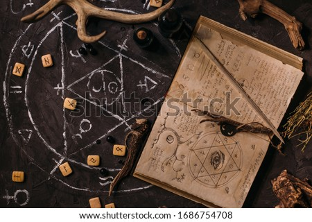 Open old book with magic spells, runes, black candles on witch table. Occult, esoteric, divination and wicca concept. Halloween vintage background Stock photo ©