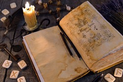 Open old book with magic spells, runes, candle and key on witch table. Occult, esoteric, divination and wicca concept. Halloween vintage background