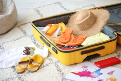 Open packed suitcase on floor in room. Travel concept