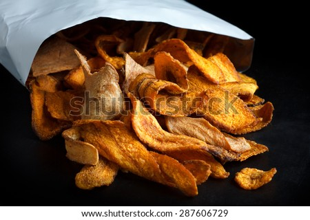 Open packet of fried parsnip and carrot chips on black.